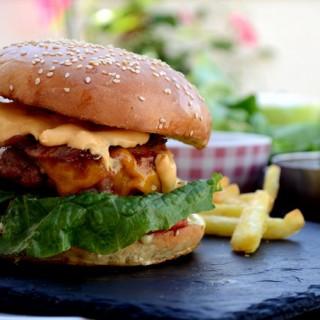 Burger με μπέικον, σάλτσα τυριού και καραμελωμένα κρεμμύδια